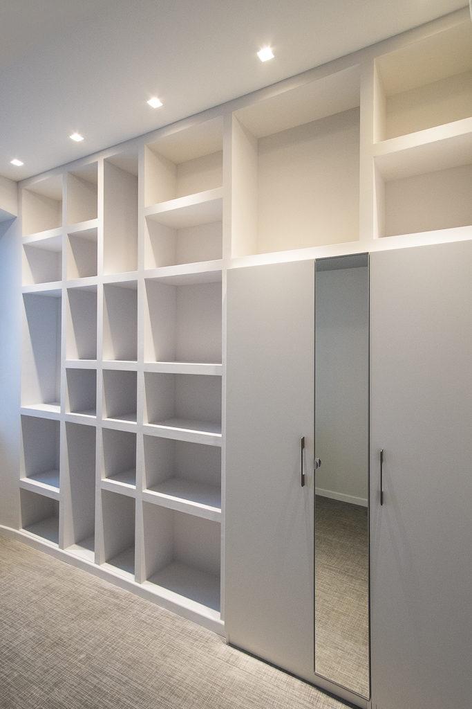Dettaglio del guardaroba integrato nella libreria con specchio sul fronte.